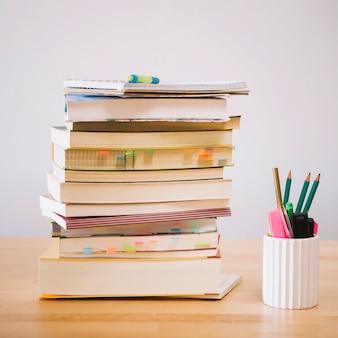 Boeken en notitieboeken dichtbij kop met potloden