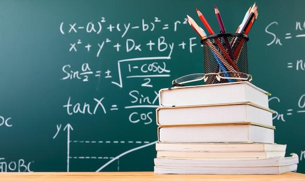Boeken en potloden op het bureau bij het schoolbord