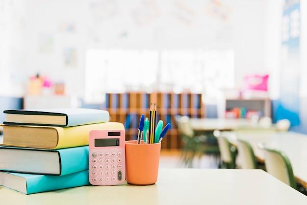 Boeken en schoolbenodigdheden in beker op tafel