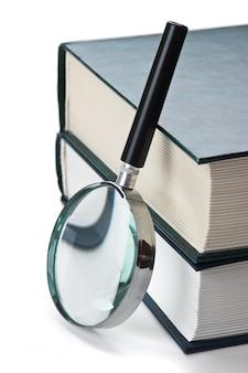 Boeken en vergrootglas op een witte achtergrond