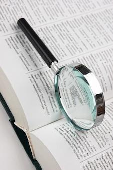Boeken en vergrootglas op witte achtergrond