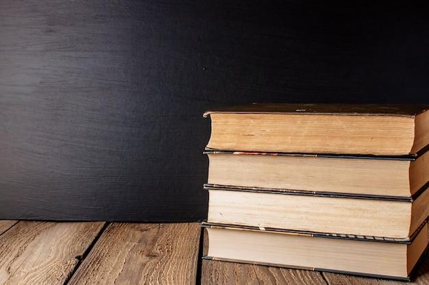 Boeken gestapeld op een houten tafel in een rustieke stijl met schoolbord.