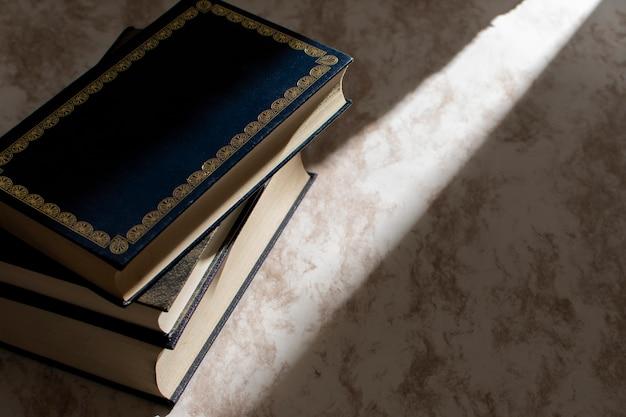Boeken gestapeld op een tafel met licht van het raam dat van de zijkant naar binnen komt