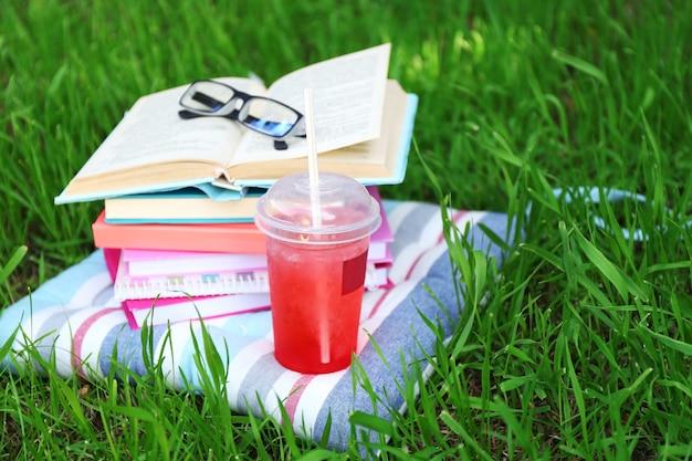 Boeken, glazen en drankje op gras close-up