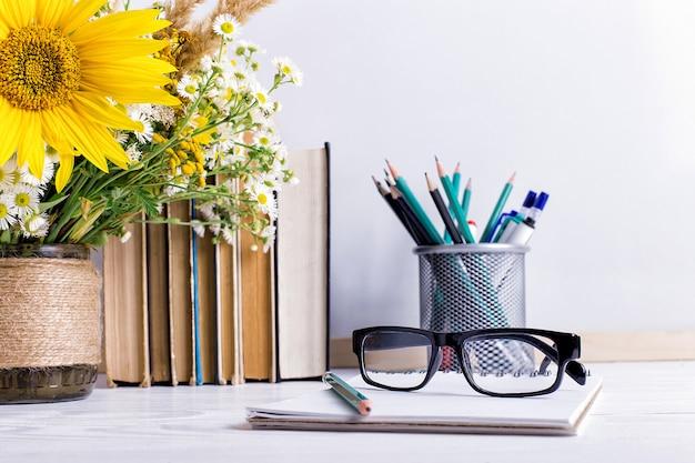 Boeken, glazen, stiften en een boeket bloemen in een vaas op wit