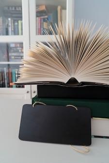 Boeken in bibliotheek, open boekpagina's met boekenplanken op de achtergrond, kopieer ruimte op zwarte leisteen