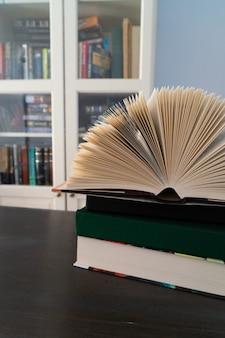 Boeken in bibliotheek, open boekpagina's met boekenplanken op de achtergrond