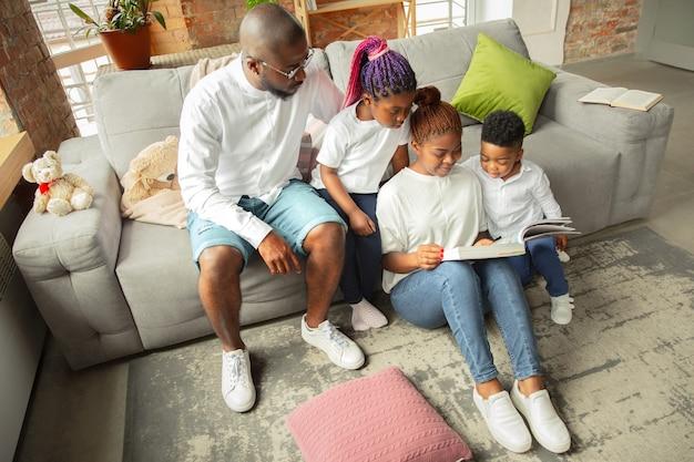 Boeken lezen jonge en vrolijke afrikaanse familie tijdens uitgaven voor quarantaine-isolatie