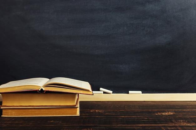 Boeken liggen op de achtergrond van het schoolbord.