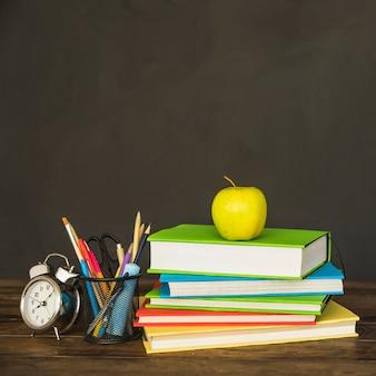 Boeken met briefpapier en klokken op tafel