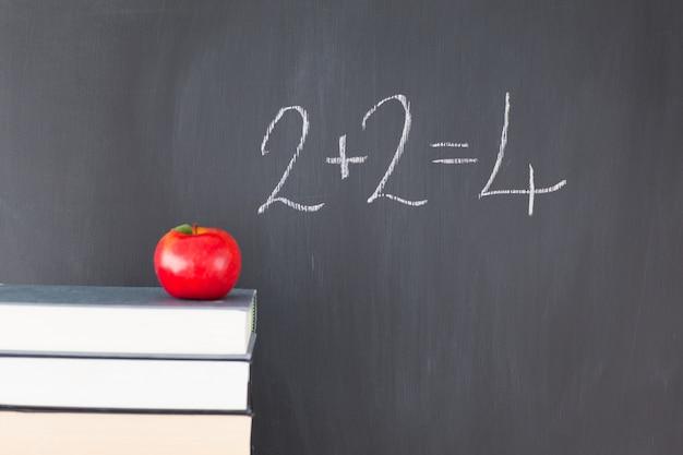 Boeken met een appel en een schoolbord