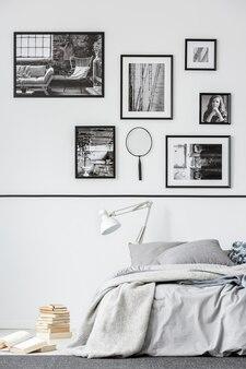 Boeken naast bed met witte lamp in grijs slaapkamerinterieur met galerij met foto's. echte foto