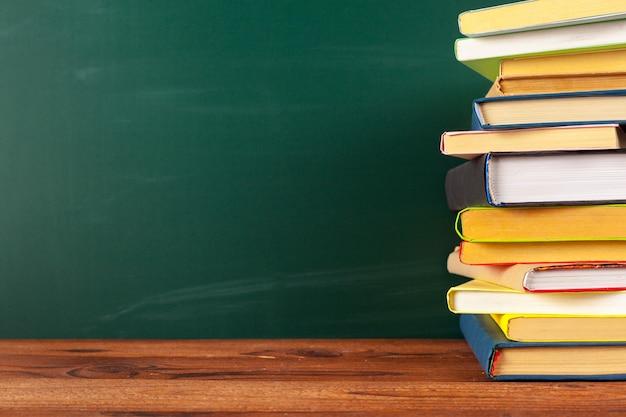 Boeken op bureau, schoolbord achtergrond met copyspace