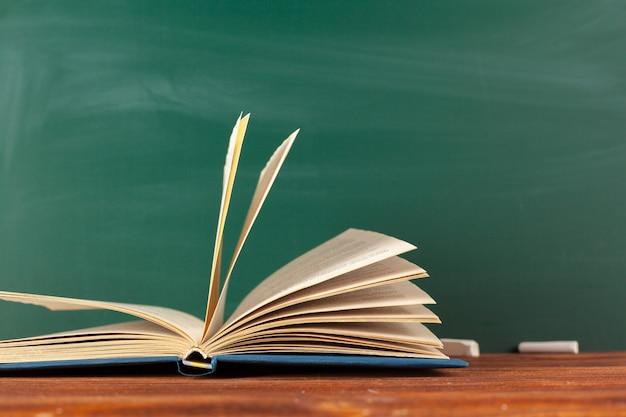 Boeken op bureau, schoolbord