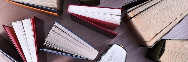 Boeken op tafel, bovenaanzicht. boeken, de vellen zijn uitgespreid in de vorm van een waaier, de schaduwen van boeken op een lichte houten tafel.