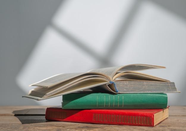 Boeken over houten tafel op witte muur