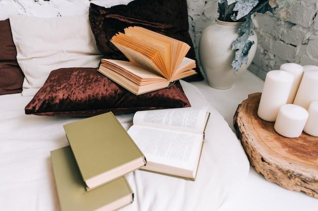 Boeken over witte bank met kussens in gezellig huis