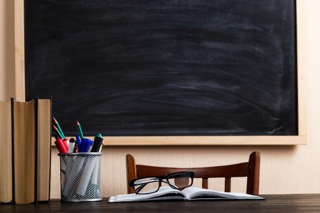 Boeken, pennen, potloden en glazen op een houten tafel, tegen een krijtbord.