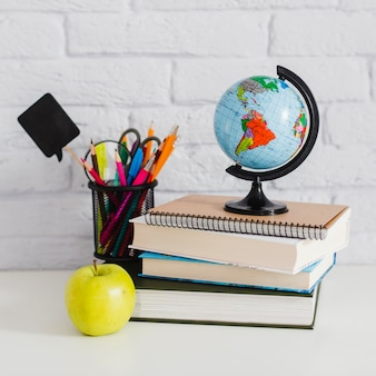 Boeken, potloden, appel en wereldbol