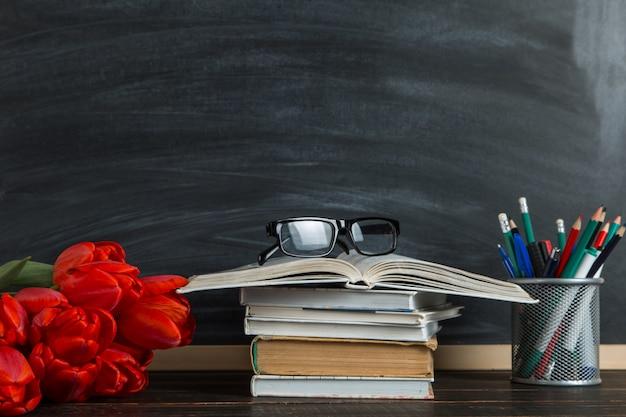 Boeken, rode tulpen en schoolbenodigdheden op blackboard
