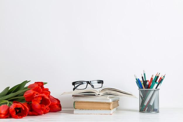 Boeken, rode tulpen en schoolbenodigdheden op wit.