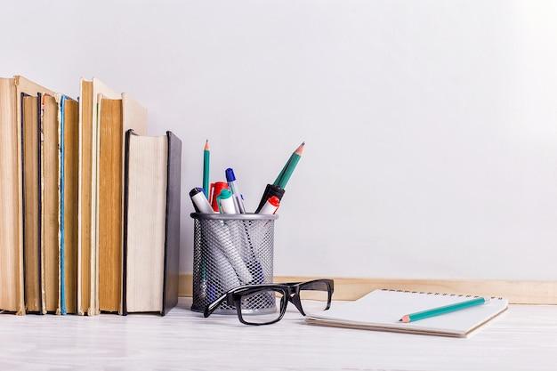 Boeken, stiften, notitieboekje, potlood en glazen op de tafel