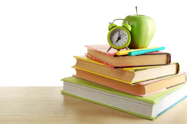 Boeken, wekker en appel op bureau, dat op wit wordt geïsoleerd