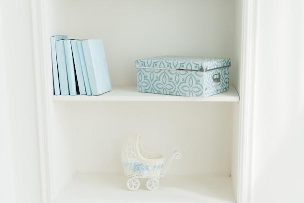 Boekenkast met blauwe boeken, kinderwagen. wit interieur. het decor van de kamer.