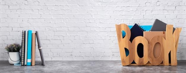 Boekenplank met boeken in houten doos op bakstenen muur