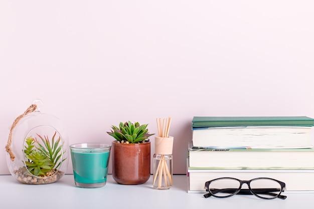 Boekenplank met veelkleurige boeken, vetplanten van kamerplanten en zwart bordframe voor tekst. achtergrond voor teacher's day, wereldboekendag. stilleven met stapel kleurrijke boeken, schoolbord