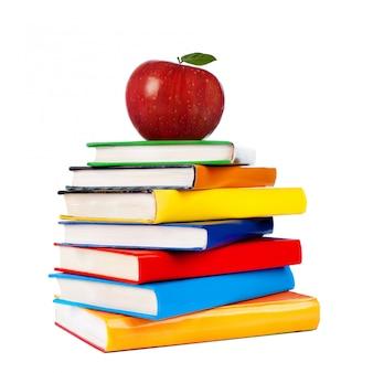Boekentoren met appel op wit wordt geïsoleerd dat