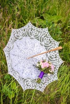 Boeket beige rozen en roze pioenrozen op een witte bruids paraplu in groen gras