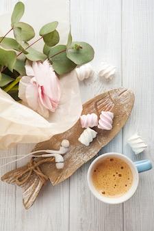 Boeket, bloem, kopje koffie, oortelefoons.