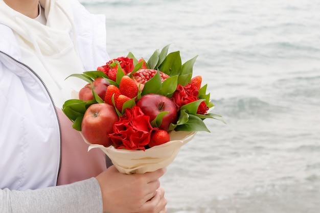 Boeket bloemen en fruit in de handen van een vrouw