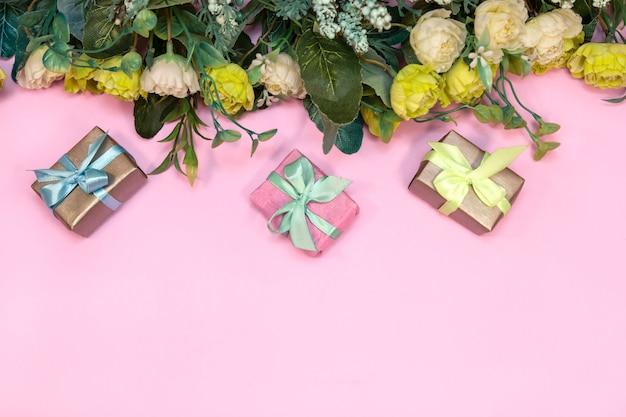 Boeket bloemen en geschenkdozen op roze achtergrond, bovenaanzicht