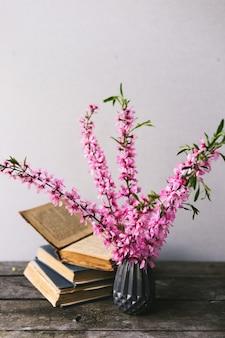Boeket bloemen en oude boeken op een oude houten plank met kopie ruimte. vintage inrichting.