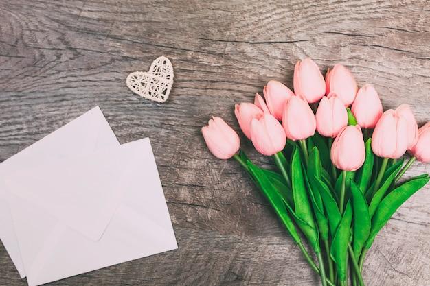 Boeket bloemen, envelop, op houten achtergrond.
