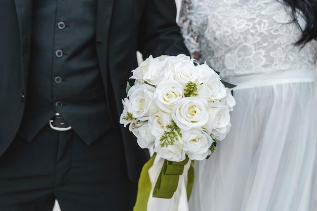 Boeket bloemen gehouden door bruidegom en bruid