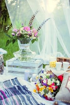 Boeket bloemen in de stijl van boho in een glazen vaas in de natuur