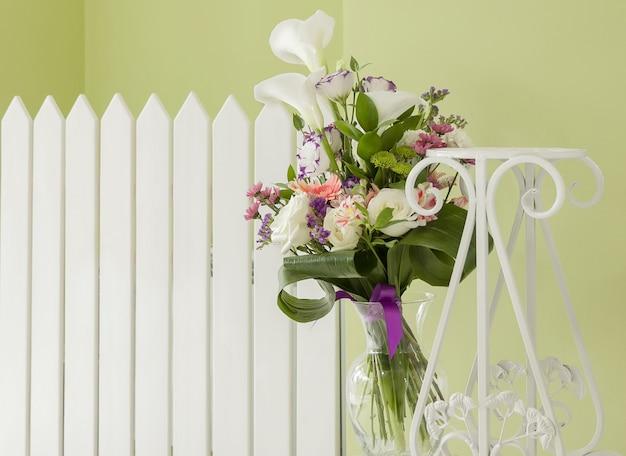 Boeket bloemen in een vaas van glas tegen een wit hek