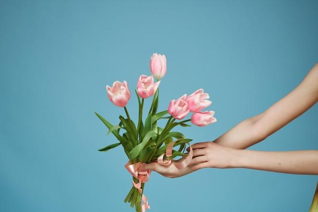 Boeket bloemen in handen romantiek cadeau blauwe achtergrond