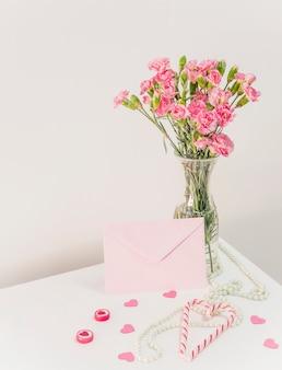 Boeket bloemen in vaas in de buurt van snoep stokken, envelop en kralen op tafel