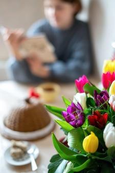 Boeket bloemen met een meisje dat op de tafel schrijft. keuken