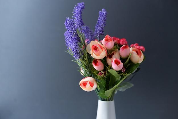 Boeket bloemen van rozen en lavendel in een witte vaas