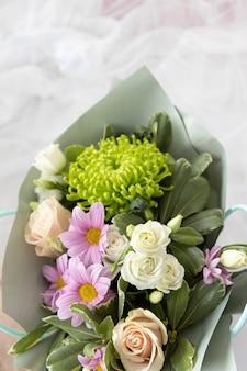 Boeket bloemen voor de bruid op een witte chiffon achtergrond. feestelijk begrip. plat leggen.