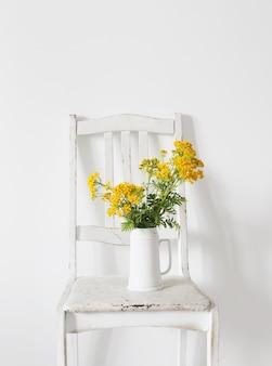 Boeket boerenwormkruid op oude houten stoel in wit interieur