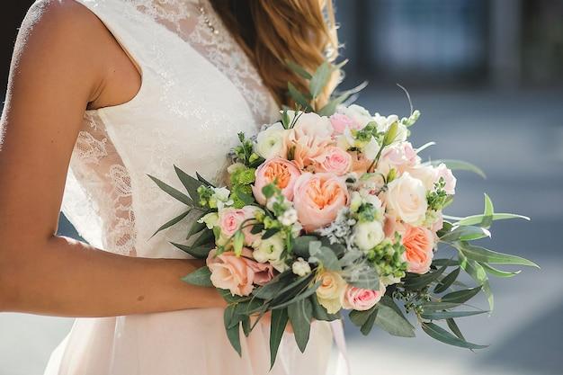 Boeket delicate rozen en eucalyptus in handen van de bruid