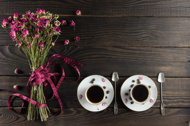 Boeket droge bloemen met een lint op het donkere houten oppervlak. twee porseleinen kopjes koffie en twee schoteltjes