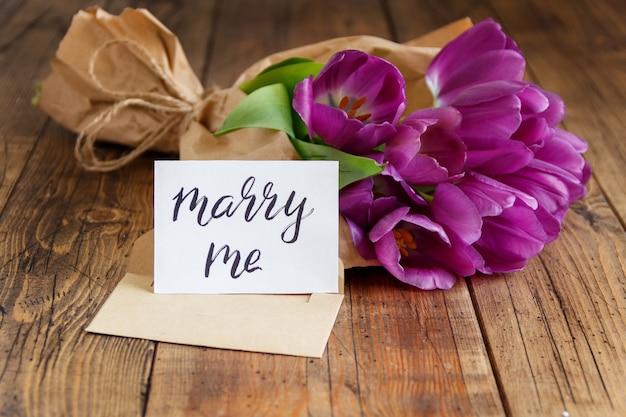 Boeket en marry me kaart op houten tafel close-up