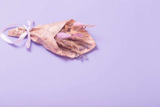 Boeket gedroogde bloemen in ambachtelijk papier op lila achtergrond